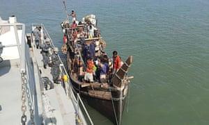 A Bangladeshi navy vessel takes a boat carrying Rohingya refugees alongside