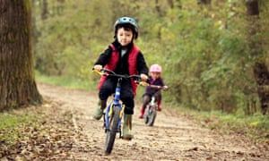 Boy and girl cycling in the woods.