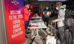 Eliud Kipchoge (right) registers at the official hotel and enters the biosecure bubble for the London Marathon on Sunday.