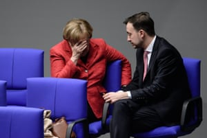 Berlin, Germany Chancellor Angela Merkel of the Christian Democratic Union (CDU) and the chair of the CDU youth organization Junge Union, Paul Ziemiak, talk in one of the back benches during a session of the German Bundestag parliament