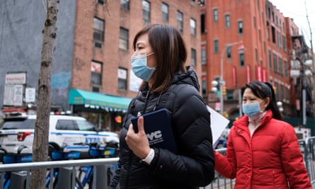 People in medical masks in New York's Chinatown. About 100 Americans, in 26 states, are being tested for the virus.