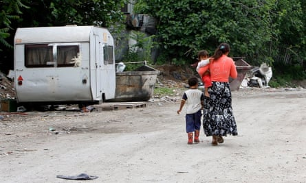 A Roma woman walks with her children in a camp in Rome.