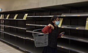 A Hong Kong shopper walks past empty supermarket shelves, usually stocked with toilet paper and kitchen rolls.