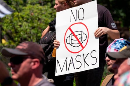 An anti-mask protestor holds up a sign in front of the Ohio Statehouse.