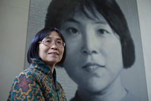 Former Red Guard Yu Xiangzhen poses in front of her picture by artist Xu Weixin.