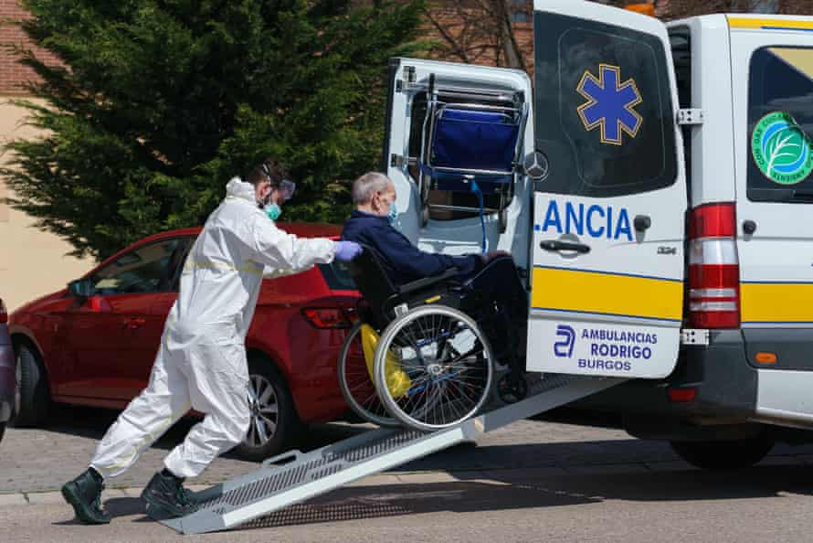 A worker pushes a man on a wheelchair outside an elderly people's nursing home in Burgos in northern Spain on Thursday.