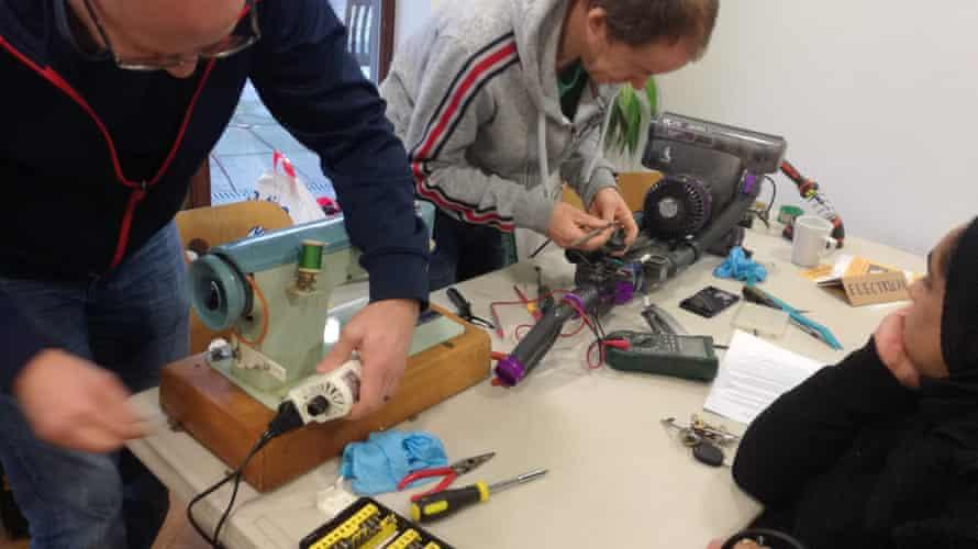 Volunteer menders get to work at Levenshulme Repair Café in Manchester.