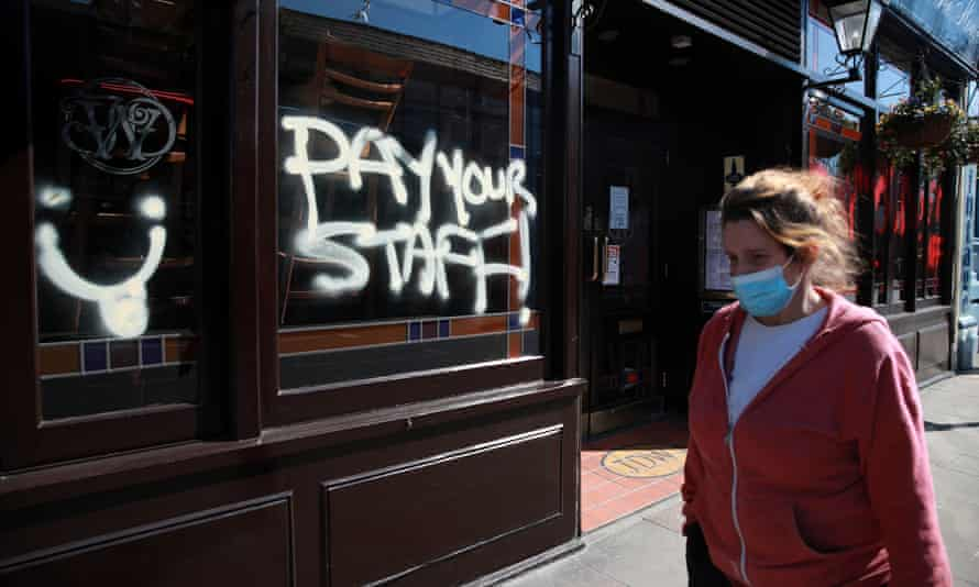 A person walks by graffiti that reads 'Pay your staff' on a JD Wetherspoon pub in Crystal Palace, south London