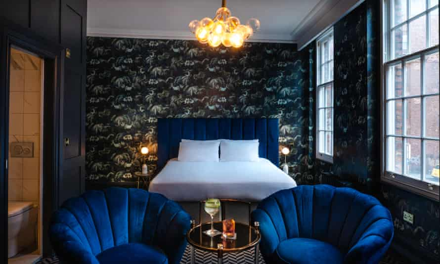 A room in the boutique hotel Lock & Key, with a royal blue headboard on the bed and two matching armchairs