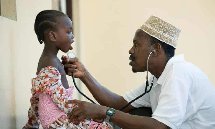 A girl is examined by a doctor at a clinic in Zanzibar.
