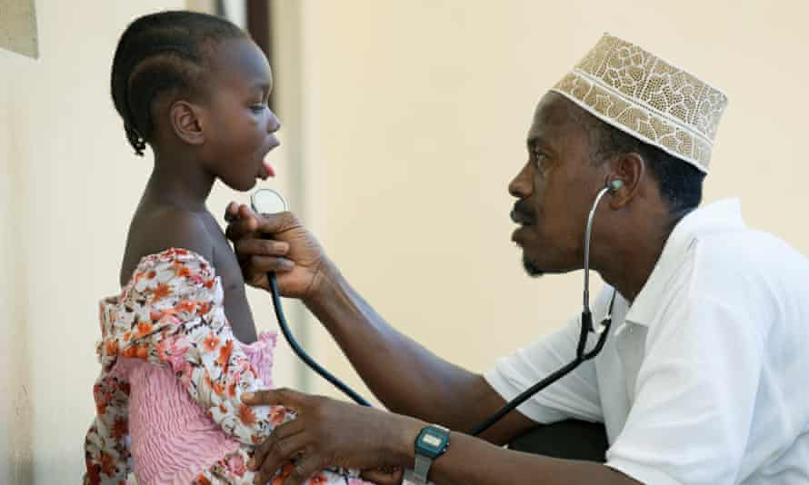 A young girl is examined by a medic at a clinic in Tanzania
