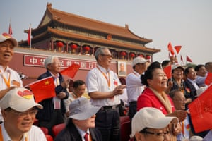 Spectators sing and wave national flags before the parade begins in Tiananmen Square