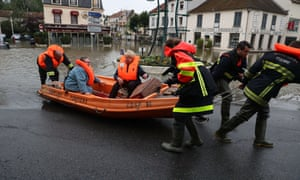 Firefighters evacuate people in a small boat from a flooded street after the Yvette river burst its banks.