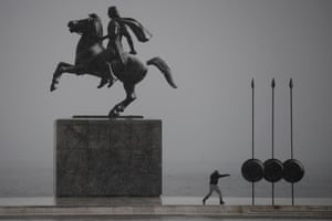 A man exercises in a snowy landscape near the statue of Alexander the Great at the seafront of Thessaloniki.