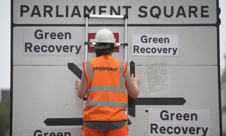 a Greenpeace protest outs up a road sign map pointing to green recovery in all directions from parliament square