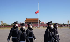 Chinese police march through Tiananmen Square before a national mourning for the victims of Covid-19
