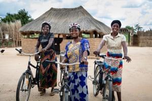 "Let to right: dairy farmers (L-R) Hilda Ndoka, Elizabeth Kankoyo and Enia Simukombwe stand with their ""pay-as-you-go"" bikes in Mukwalantila village, near Zimba, Zambia."