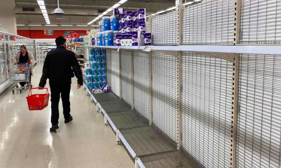 A shopper walks past near-empty shelves of toilet paper at a supermarket in a Melbourne