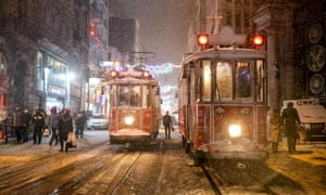People walk through a snowfall in Istanbul.