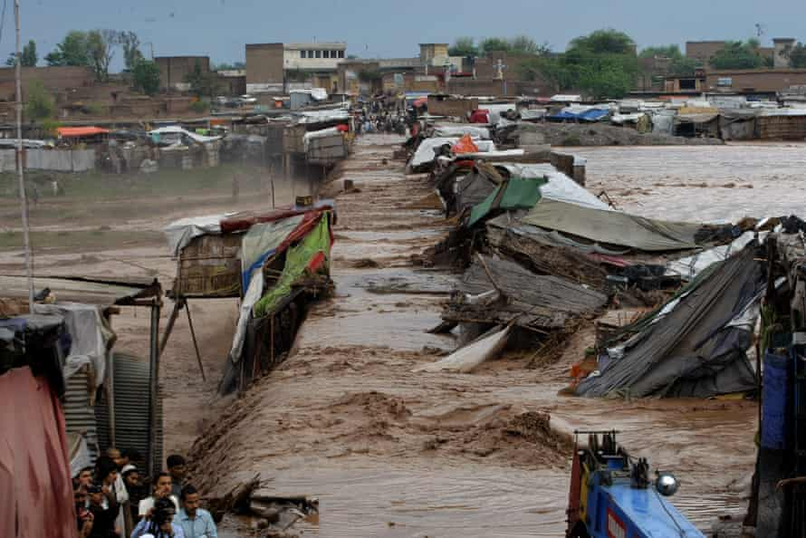 Villagers stand outside their homes during flash floods on the outskirts of Peshawar, Pakistan, April 2016