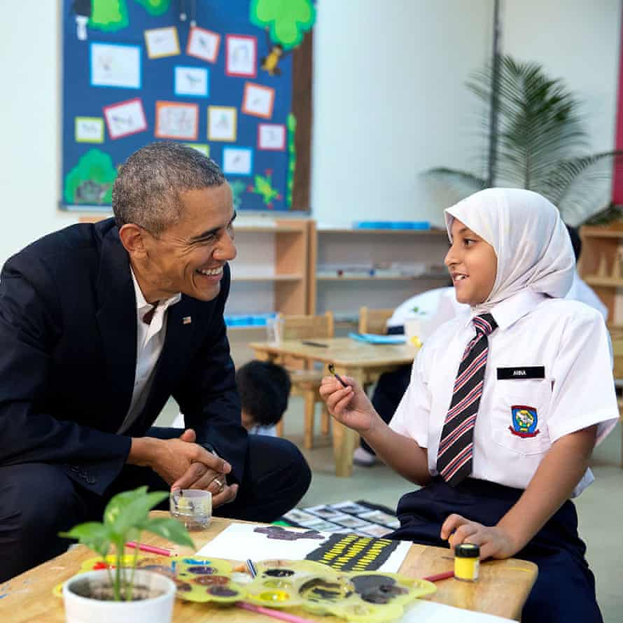 former president Barack Obama kneeling at the school desk of a young refugee painting a picture