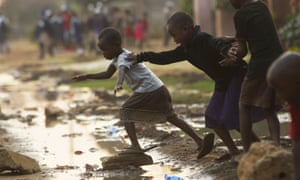Children jump over raw flowing sewage on the streets of Harare, Zimbabwe, amid a cholera outbreak in the country which has killed at least 30 people.