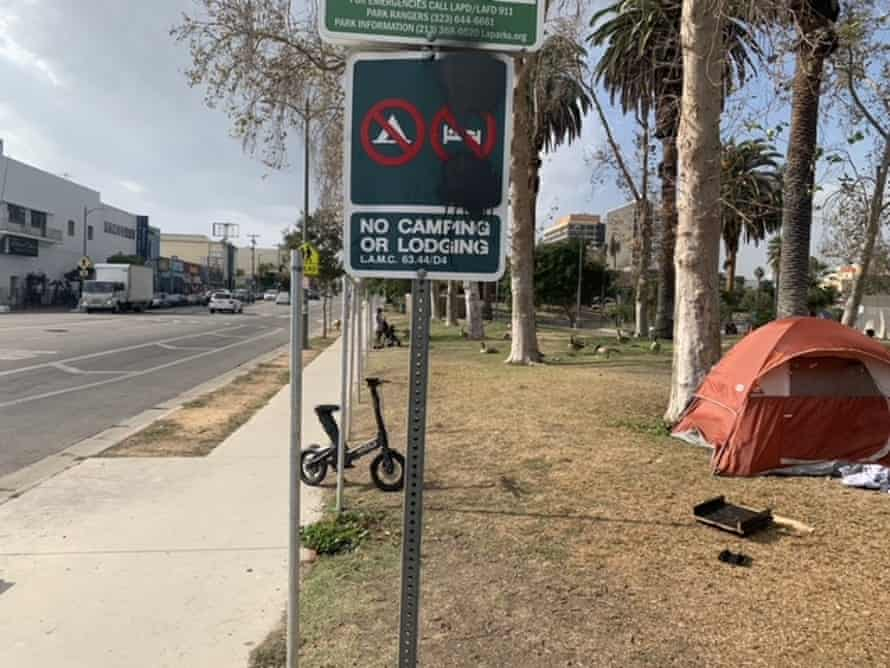 A tent has been placed near a 'No camping' sign at MacArthur Park in Los Angeles.