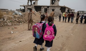 Schoolchildren walk on a road cleared of IED devices in Fallujah, Iraq