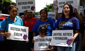 "Women in El Salvador hold placards that read: ""Freedom, justice and reparation"" and ""Justice for Evelyn"""