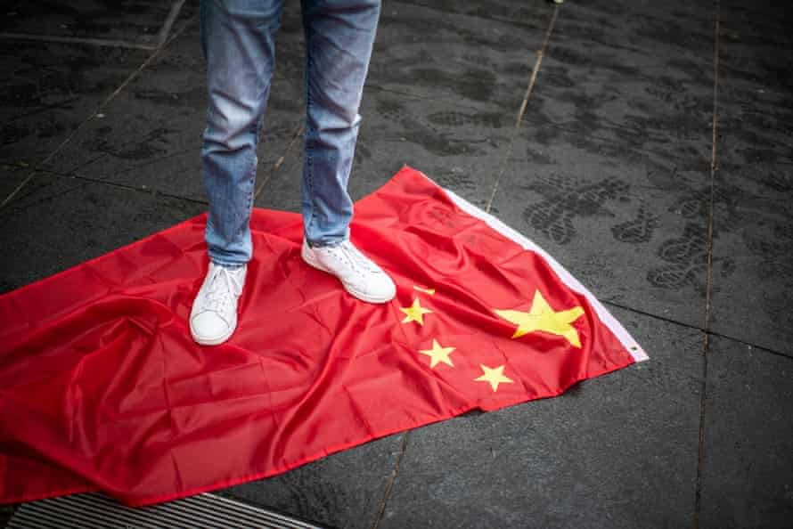 A person standing on the Chinese flag June 4, 2021 during the protests outside the Chinese Embassy in London on the anniversary of the Tiananmen Square Massacre.