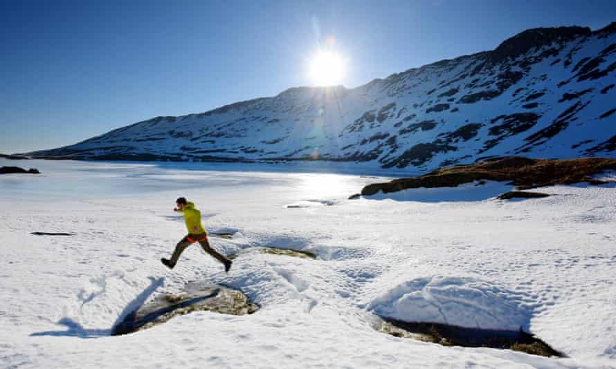 A walker at Red Tarn on Helvellyn in the Lake District. Some areas of the UK are set to feel colder than places in the Arctic circle this week.