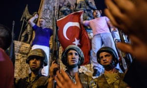 Civilians protesting against the coup attempt stand above Turkish soldiers in Taksim Square.