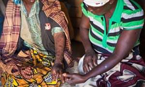 A woman who is very unwell with Aids, with a friend and carer in a village in Manica District, Mozambique