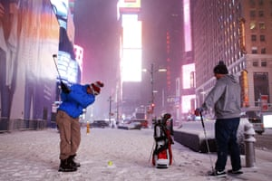 Two men play golf with a tennis ball as the snow storm swept through Times Square in NYC