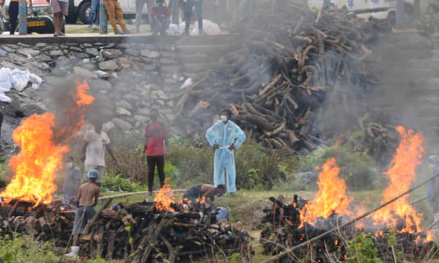 Workers cremate people who have died of Covid-19 at a crematorium outside Siliguri on Tuesday. Epidemiologists believe the country's reported death toll is only a fraction of the true figure.