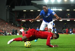 Divock Origi of Liverpool falls after battling with Yerry Mina of Everton.