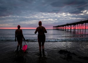 Two women enter the North Sea for a swim in Saltburn-by-the-Sea, North Yorkshire