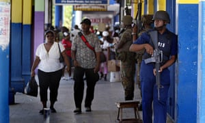 Armed police stand guard at a shopping centre in Kingston, Jamaica