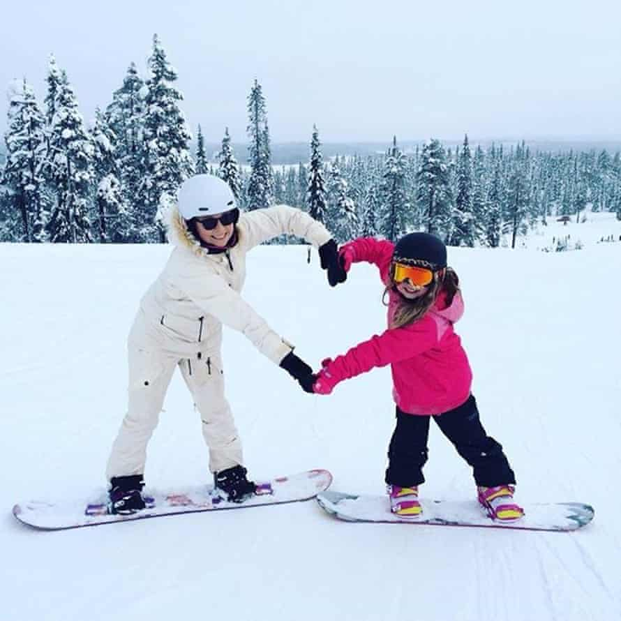 A mother and daughter forming a heart with their arms while snowboarding
