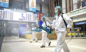 A photo released by China's Xinhua News Agency showing workers spraying disinfectant in the central hall of the Beijing railway station.