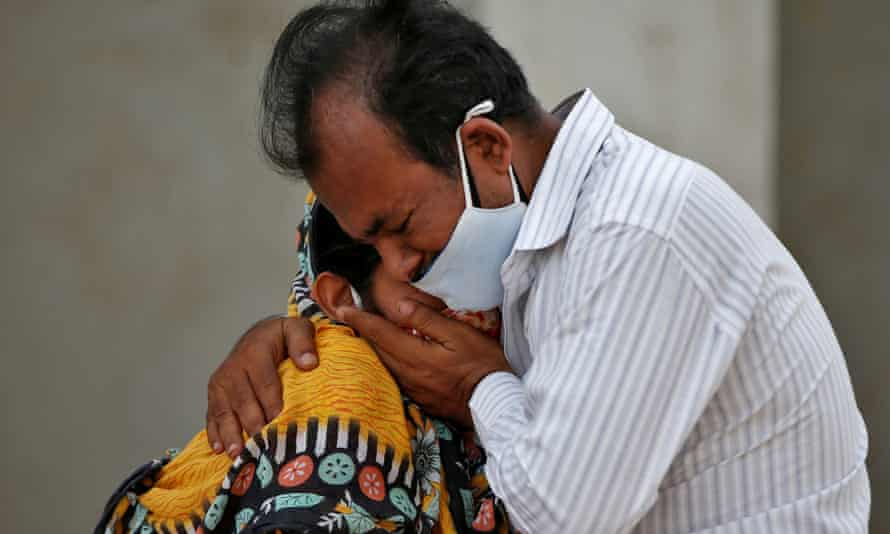 A weeping Indian man in a mask hugs an Indian woman