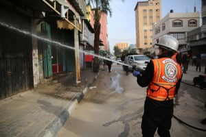 Palestinian civil defence workers sterilise streets of the Nuseirat refugee camp in the Gaza Strip to prevent the spread of the coronavirus