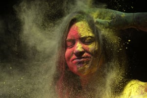 Mumbai, India. A man smears a woman's face with coloured powder during celebrations marking the Holi festival, which heralds the arrival of spring