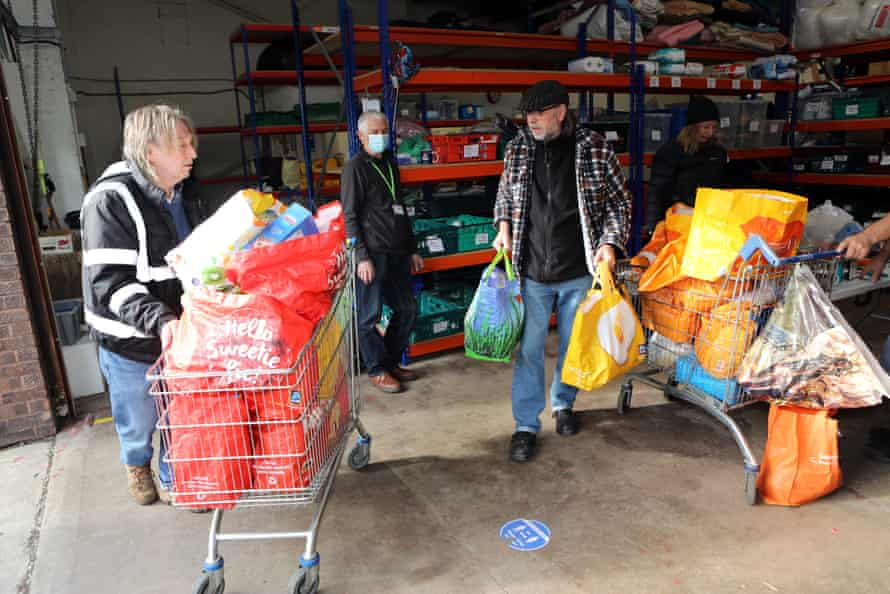 Volunteers at the Welcome Centre warehouse unpack and sort food donations.