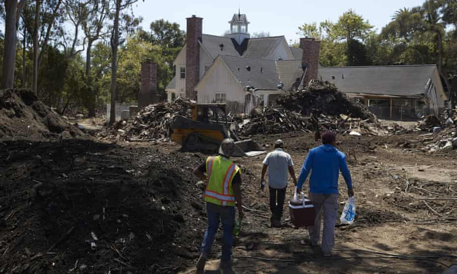 Workers walk past a pile of mud and debris outside a home heavily damaged by a mudslide in Montecito, California.