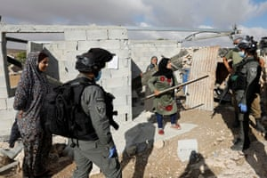 A Palestinian woman argues with Israeli border police officers who want to stop her building a house in the village of Susya in the Israeli-occupied West Bank.