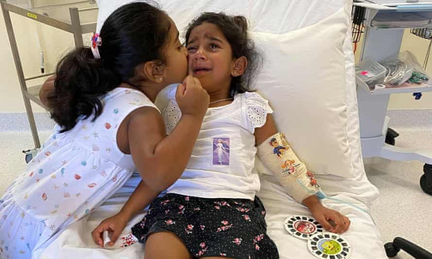Kopika Murugappan comforts her three-year-old sister Tharnicaa