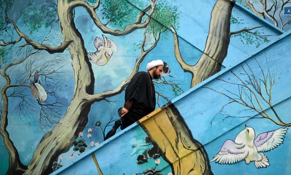 A man walks past a mural in Tehran.