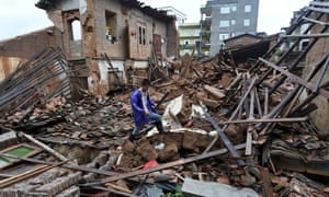 A man walks over the wreckage of houses hit by super typhoon Nepartak in Putian city in Fujian province on Saturday.