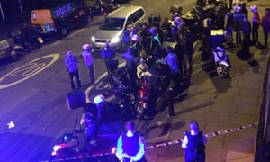 Drivers and police in the street after officers said two men on a moped had carried out a string of acid attacks.